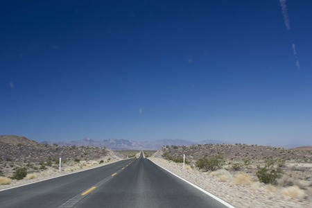 DEATH VALLEY, USA - AUGUST 8 2013: The street to Death Valley, a straight highway in the american desert, on a sunny day in August. Stock Photo