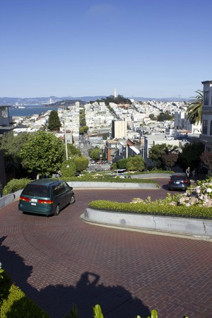 switchback: SAN FRANCISCO, USA - AUG 11 2013: The famous Lombard Street in San Francisco, famous for its steep, one-block section with eight hairpin turns, with a car crossing it and San Francisco Cityscape.