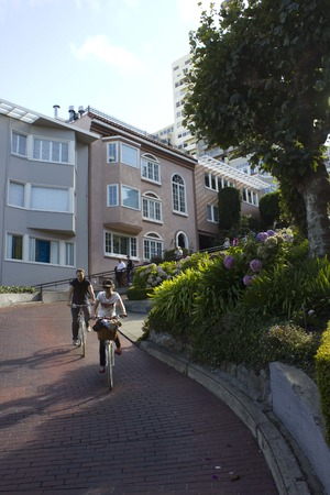 switchback: SAN FRANCISCO, USA - AUG 11 2013: The famous Lombard Street in San Francisco, famous for its steep, one-block section with eight hairpin turns, with two person on a bycicle.