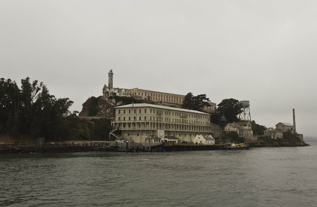 ancient prison: ALCATRAZ, USA - AUGUST 12 2013: Arriving in Alcatraz Penitentiary. External view of the building in a dull day in the summer season. Editorial