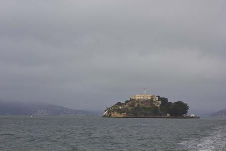 ALCATRAZ, USA - AUGUST 12 2013: View of Alcatraz island from the distance, in a dull and foggy day