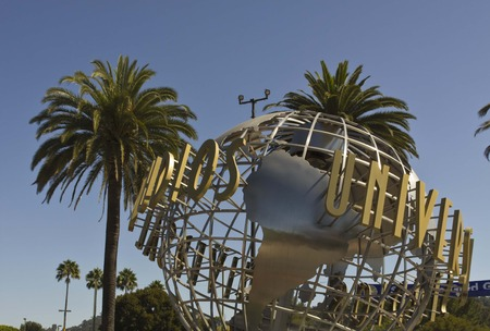 hollywood: LOS ANGELES, CALIFORNIA - AUG 17 2013: Universal Studios Hollywood sign at the entrance of the amusement Park, suroounded by palms