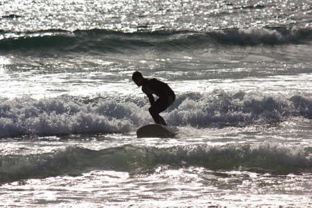 individual sport: SAN DIEGO, USA - AUGUST 20 2013: Surfer at sunset in San Diego beach