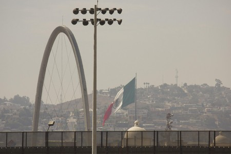 confines: SAN DIEGO, USA - AUGUST 20 2013: Boundary line between United States and Mexico, from San Diego looking at Tijuana Revolucion Arch Editorial