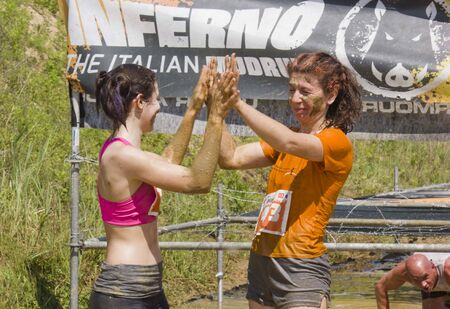mud splatter: SIGNA, ITALY - MAY 9 2015: two women celebrates the end of the Mud Run near Florence, beating their hands Editorial