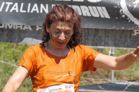 mud splatter: SIGNA, ITALY - MAY 9 2015: A woman with the face dirt with mud during the Mud Run competition near Florence on May 2015 Editorial