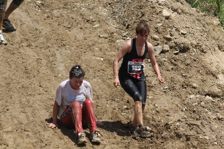muddy clothes: SIGNA, ITALY - MAY 9 2015: Two women  going down on a steep slope, all dirt with mud, during the Inferno Run competition near Florence Editorial