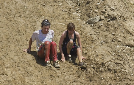 run down: SIGNA, ITALY - MAY 9 2015: Two women  going down on a steep slope, all dirt with mud, during the Inferno Run competition near Florence Editorial