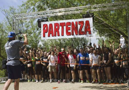 inferno: SIGNA, ITALY - MAY 9 2015: Athletes ready to go at the starting line of the Inferno Run competition near Florence, Italian Mud Run