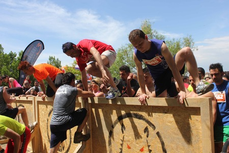 SIGNA, ITALY - MAY 9 2015: Group of people jumping over an obstacle during the Inferno Run mud Race in Florence Stock Photo - 41648094