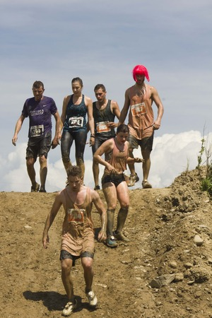 run down: SIGNA, ITALY - MAY 9 2015: Participant at Inferno Run near Florence going down on a steep slope, all dirt with mud