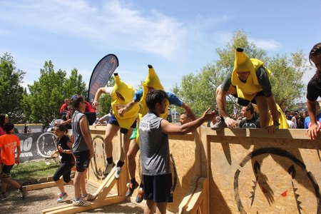 inferno: SIGNA, ITALY - MAY 9 2015: Group of people dresssed as bananas jumping over an obstacle during the Inferno Run mud Race in Florence