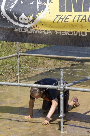 muddy clothes: SIGNA, ITALY - MAY 9 2015: Man passing under the wires in a mud ground during a mudrun competition in Italy Editorial