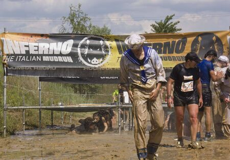 muddy clothes: SIGNA, ITALY - MAY 9 2015: Man dressed as a sailor after passing under the wires, all dirt with mud