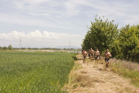 bare breast: SIGNA, ITALY - MAY 9 2015: Men with bare breast running in a field in Tuscany, during the Inferno Run competition