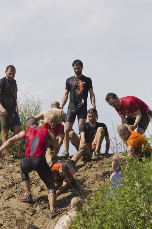 muddy clothes: SIGNA, ITALY - MAY 9 2015: Solidarity through the participant at Mud run near Florence, helping each other in climbing a muddy rise Editorial