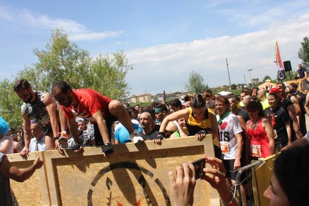 inferno: SIGNA, ITALY - MAY 9 2015: Group of people jumping over an obstacle during the Inferno Run mud Race in Florence