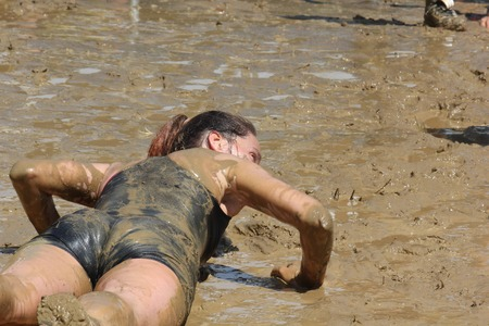 muddy clothes: SIGNA, ITALY - MAY 9 2015: A woman lie down in the mud during the Mud Run competition near Florence on May 2015 Editorial