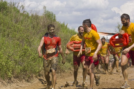 muddy clothes: SIGNA, ITALY - MAY 9 2015: Baywatch team at the mud run competition near florence, all dirt with mud