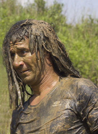 mud splatter: SIGNA, ITALY - MAY 9 2015: Portrait of a man dirt with mud during a Mud Run competition in Italy Editorial