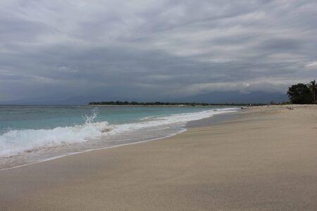 dull: Tropical Indonesian Gili Islands beach waters edge in a dull day