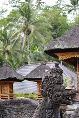 balinese: Balinese statue with traditional architecture and plants Stock Photo