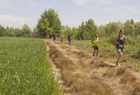 gens courir: SIGNA, ITALY - MAY 9 2015: Group of people running outdoor in a field in Tuscany, during the Inferno Run competition
