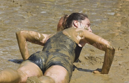 run down: SIGNA, ITALY - MAY 9 2015: A woman lie down in the mud during the Mud Run competition near Florence on May 2015 Editorial