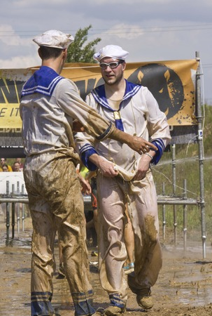 muddy clothes: SIGNA, ITALY - MAY 9 2015: Two men dressed as seamans with clothes dirt of mud during a mudrun competition