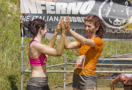 muddy clothes: SIGNA, ITALY - MAY 9 2015: two women celebrates the end of the Mud Run near Florence, beating their hands Editorial