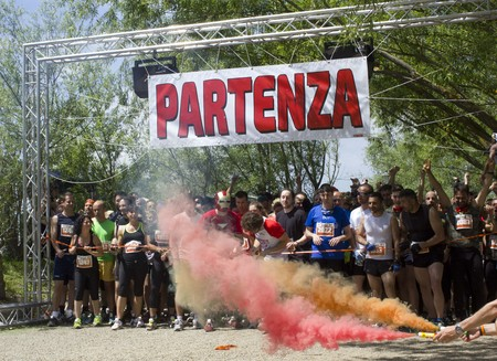 gun shot: SIGNA, ITALY - MAY 9 2015: Colored gun shot at the beginning of Inferno Run Mud Race near Florence, with people starting to run