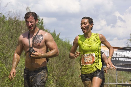 muddy clothes: SIGNA, ITALY - MAY 9 2015: Couple of participant at an Italian Mud Run while running all dirt with mud