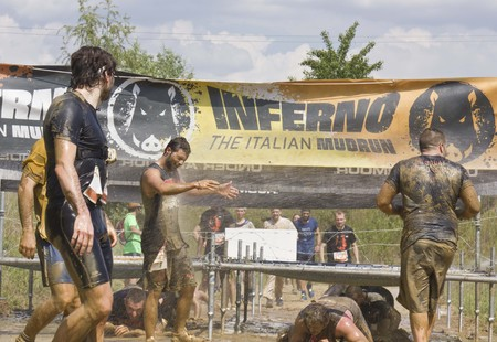 muddy clothes: SIGNA, ITALY - MAY 9 2015: People passing  under the wires during the Inferno Run Mud Race competition near Florence, splashing in the mud Editorial