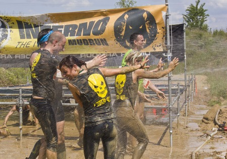 mud splatter: SIGNA, ITALY - MAY 9 2015: People passing  under the wires during the Inferno Run Mud Race competition, while civil protection splash water to them