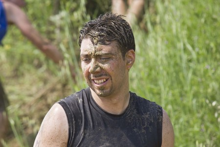 muddy clothes: SIGNA, ITALY - MAY 9 2015: Portrait of a man dirt with mud during a Mud Run competition in Italy Editorial