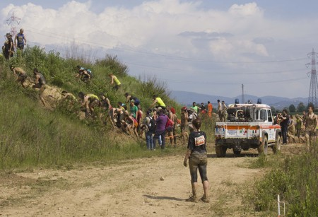 muddy clothes: SIGNA, ITALY - MAY 9 2015: People climbing a muddy rise during a mud run competition near Florence, with an ambulance in the background Editorial