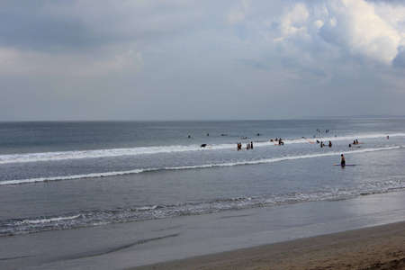 kuta: BALI, INDONESIA - JULY 13 2012: Group of people surf on Kuta beach in Indonesia