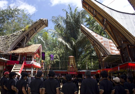 indonesia people: TANA TORAJA, INDONESIA: People in black at a funeral ceremony in the Sulawesi, with the traditional torajan houses Editorial