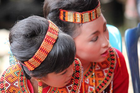 celebes: TANA TORAJA, INDONESIA - JULY 3 2012: Portrait of two young Torajan girls in traditional costume at a funeral ceremony