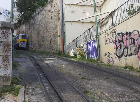 LISBON, PORTUGAL - OCTOBER 25 2014: Lisbon Lavra funicolar arriving on the narrow steep street Editorial