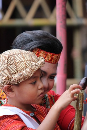 celebes: TANA TORAJA, INDONESIA - JULY 3 2012: Young Indonesian boy playing with his sister during a ceremony in Tana Toraja, Indonesia, traditionally dressed Editorial