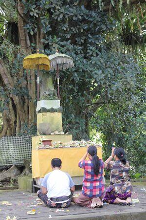 hinduist: BALI, INDONESIA - JULY 7 2012: Three Balinese people praying outdoor Editorial