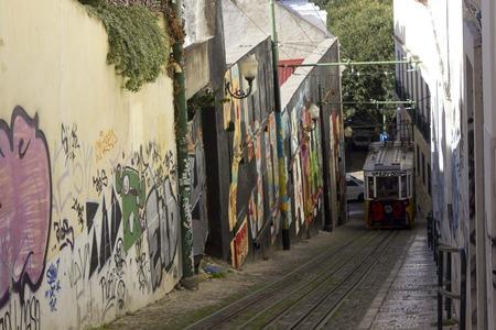 LISBON, PORTUGAL - OCTOBER 25 2014: Lisbon Lavra funicolar arriving on the narrow street full of graffiti Editorial