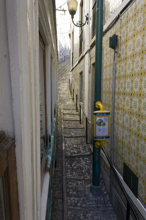 ascensor: The very narrow and slope Lavra Street in Lisbon, Portugal, with stairs with azulejos on the wall and tram stop