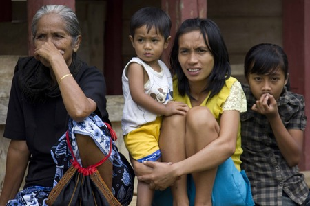 RANTEPAO, INDONESIA - JULY 3 2012: Portrait of a poor Torajan family outside their house in Rantepao, Indonesia