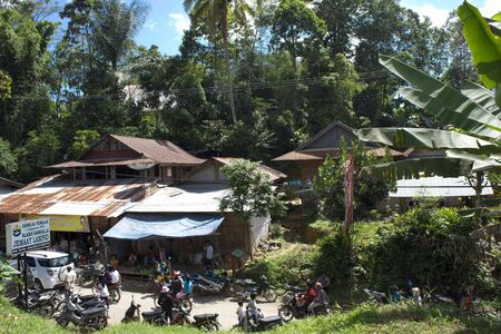 celebes: TANA TORAJA, INDONESIA - JULY 4 2012: Traditional Torajan Village, with people along the street, immersed in nature Editorial