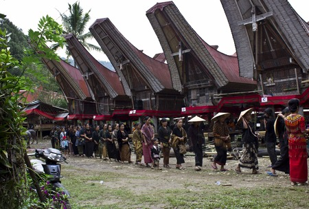 traditional house: TANA TORAJA, INDONESIA - JULY 3 2012: People procession at a traditional funeral ceremony, with typical tongkonan house in the background Editorial