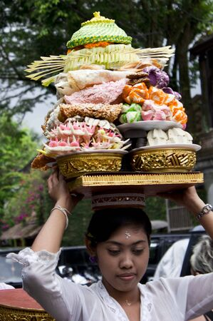 hinduist: BALI, INDONESIA - JULY 6 2012: Balinese Woman carrying food on her head in the streets of Ubud, Bali