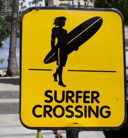 kuta: BALI, INDONESIA - JULY 7 2012: Surfer crossing warning sign on Kuta Beach in Bali