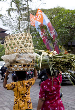hinduist: BALI, INDONESIA - JULY 6 2012: Two balinese woman from the backside carrying baskets on their heads